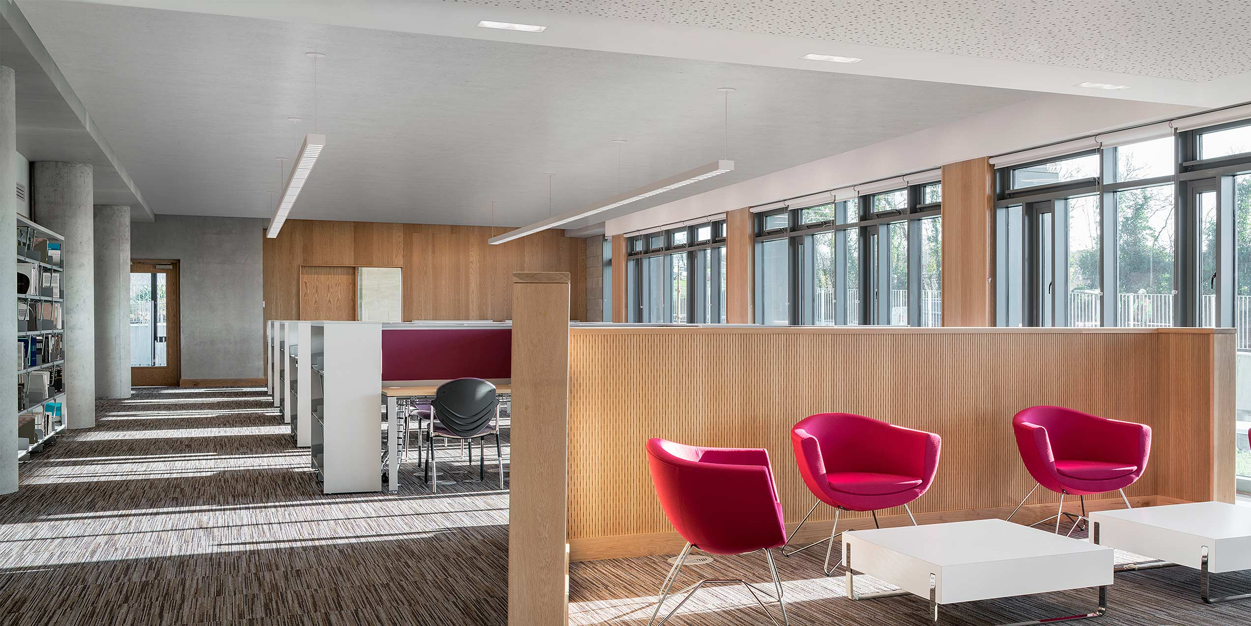 workspace area in a library that has aperture lighting fixtures. pink chairs seated around a table